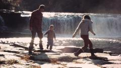 Family Playing Outdoors by waterfall in autumn Stock Footage