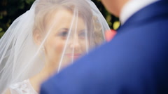 Groom lifting veil off beaming brides face on their wedding day  shot in slow - stock footage