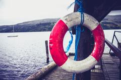Stock Photo of Life buoy hanging on pier at lake