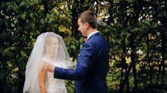 Groom lifts veil and kisses bride  shot in slow motion  close up - stock footage