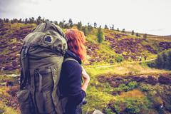 Woman with backpack watching fellow hillwalkers in the distance - stock photo