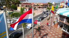 Pan from colorful Royal Plaza Mall to the Dutch and Aruban flag Stock Footage