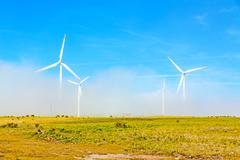 Stock Photo of wind turbines in natural green landscape - blue sky