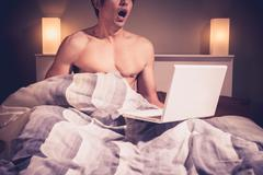 Young man is sitting in bed and watching pornography on laptop Kuvituskuvat