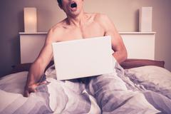 Young man is sitting in bed and watching pornography on laptop - stock photo