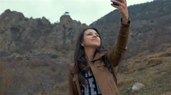 Pretty girl makes selfie with her smart phone. Toned image Stock Footage