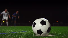 Close up of a soccer ball being kicked in slow motion at night Stock Footage