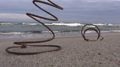 old rusty metal spring on ocean beach and waves - stock footage