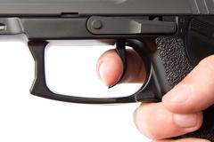 Pushing the handgun trigger - stock photo