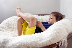 Boy (2-3) lying down in armchair with digital tablet Stock Photos
