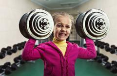 Little girl with dumb-bells Stock Photos