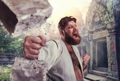 Strong karateka breaks a brick - stock photo