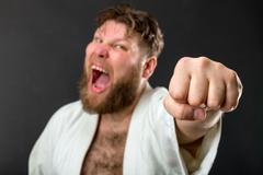 Mad strong karateka in white kimono over grey - stock photo