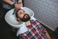 Stock Photo of Hairdresser washing hair of young man with beard