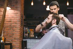 Young hairstylist making men's haircut to a bearded male - stock photo