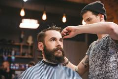 Skillful barber cutting hair of young man with beard - stock photo