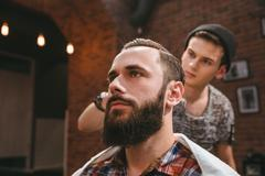 Stock Photo of Modern barber combing hair of client with beard at barbershop