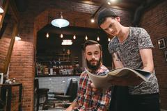 Young hairstylist and bearded client looking through magazine - stock photo