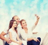 happy family with camera at home - stock photo