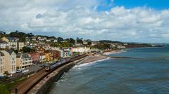 United Kingdom, England, Dawlish, Cross country train passing alongside seaside - stock photo