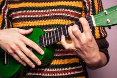 Young woman playing ukulele Kuvituskuvat