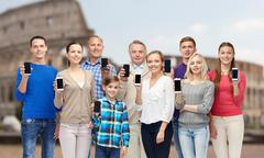 Stock Photo of group of people with smartphones over coliseum