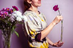 Young woman arranging a bouquet of flowers - stock photo