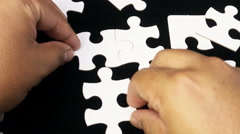 Time Lapse/stop motion - completing a white puzzle on black background. 4k video - stock footage