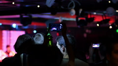 Holding up in air smartphone shooting concert and a bottle of alcohol drink Stock Footage