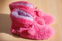 Stock Photo of Pink fur slippers on the wooden floor, sun light and shadow