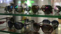 Sunglasses in a store front showcase of a shop Stock Footage