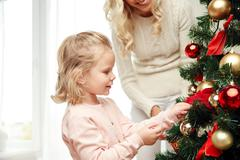 Stock Photo of happy family decorating christmas tree at home