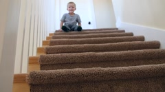 Slow motion cute little boy bouces down stairs on bum Stock Footage