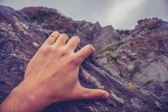 Man's hand on rock Stock Photos