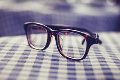 Pair of glasses on a checkered table cloth - stock photo