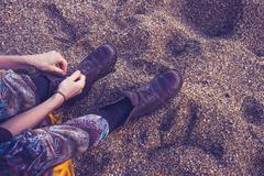 Woman tying her boot laces on the beach - stock photo