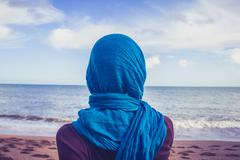 Rear view of woman with headscarf looking at the sea - stock photo