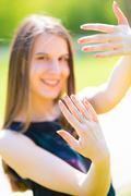 A girl shows nails outdoor in summer park Stock Photos