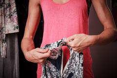 Young woman mending her clothes at home - stock photo