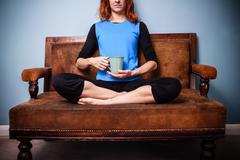 Young spiritual woman sitting on sofa drinking calming tea Stock Photos