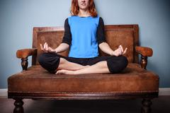 Spiritual young woman is meditating on an old sofa - stock photo