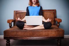 Spiritual woman sitting on sofa using her laptop Stock Photos