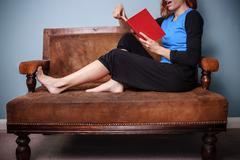 Young woman sitting on sofa reading an exciting book - stock photo