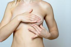 Bare Woman Holding her Breast Against Gray - stock photo