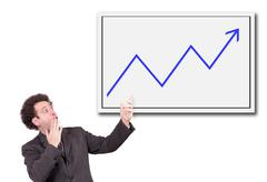 Shocked man in a suit shows a hand on the board with growing curve Stock Photos