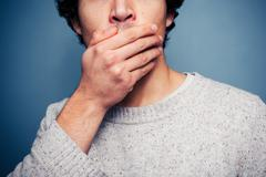 Shocked young man with his hand on his mouth - stock photo