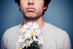 Sad and rejected man with a bouquet of flowers - stock photo