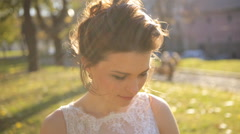 Young beautiful bride standing in the park  and straightens hair shot in slow Stock Footage