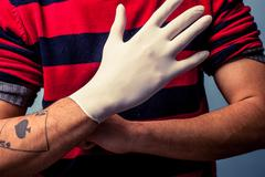Tattoo artist putting on latex glove - stock photo