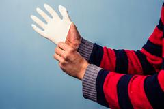 Putting on rubber glove - stock photo